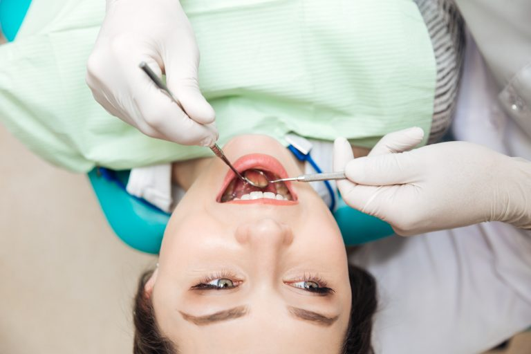 Close Up Of Patient Open Mouth During Oral Inspection