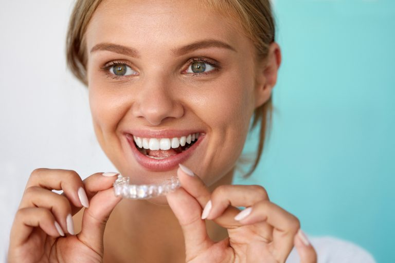 Smiling Woman With Beautiful Smile Using Teeth Whitening Tray. High Resolution Image